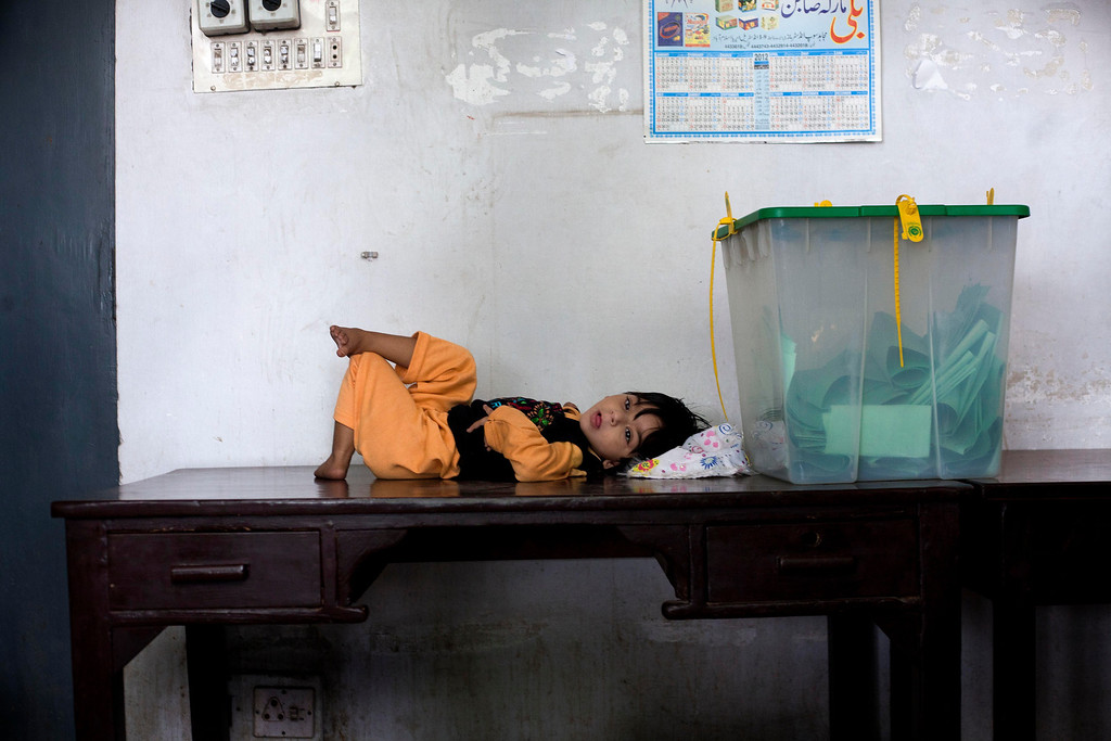 . A Pakistani child lies next a ballot box at a polling station in Islamabad, Pakistan, Saturday, May 11, 2013. Defying the danger of militant attacks, Pakistanis streamed to the polls Saturday for a historic vote pitting a former cricket star against a two-time prime minister and an unpopular incumbent. But attacks that killed and wounded dozens of people underlined the risks many people took just casting their ballots. (AP Photo/Myra Iqbal)