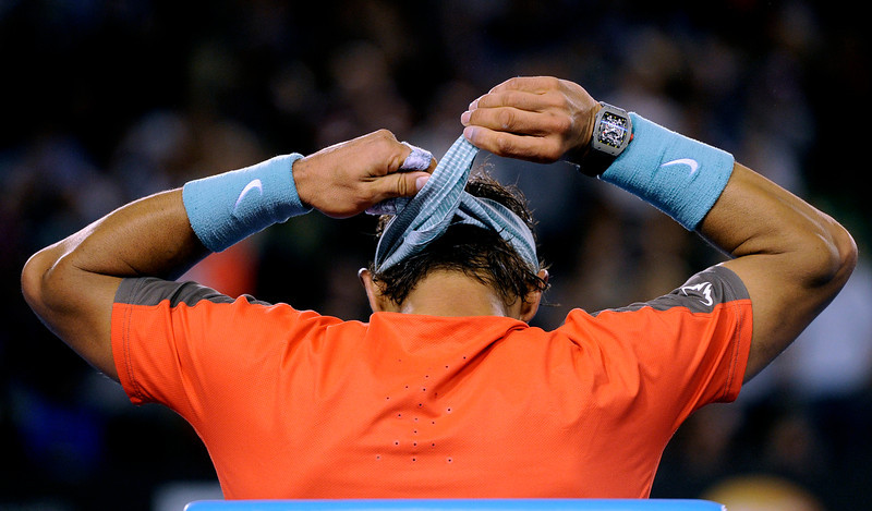 . Rafael Nadal of Spain ties his headband during a break in the semifinal against Roger Federer of Switzerland at the Australian Open tennis championship in Melbourne, Australia, Friday, Jan. 24, 2014.(AP Photo/Andrew Brownbill)