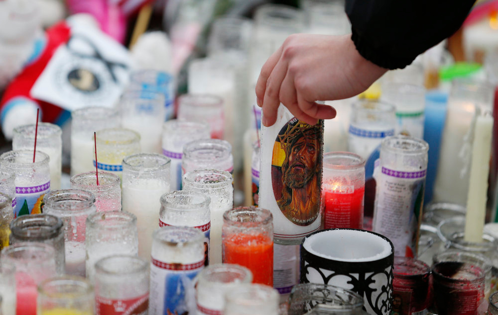 Description of . Ryan Bartolotta, 17, picks up a candle to drain out rainwater and light it on a makeshift memorial in the Sandy Hook village of Newtown, Conn., as the town mourns victims killed in a school shooting, Monday, Dec. 17, 2012. Authorities say a gunman killed his mother at their home and then opened fire inside the Sandy Hook Elementary School in Newtown, killing 26 people, including 20 children, before taking his own life, on Friday. (AP Photo/Julio Cortez)