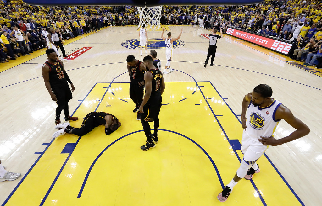 . Golden State Warriors forward Kevin Durant (35) walks past as Cleveland Cavaliers forward LeBron James, on ground, is checked on by teammates during the first half of Game 1 of basketball\'s NBA Finals in Oakland, Calif., Thursday, May 31, 2018. (AP Photo/Marcio Jose Sanchez, pool)