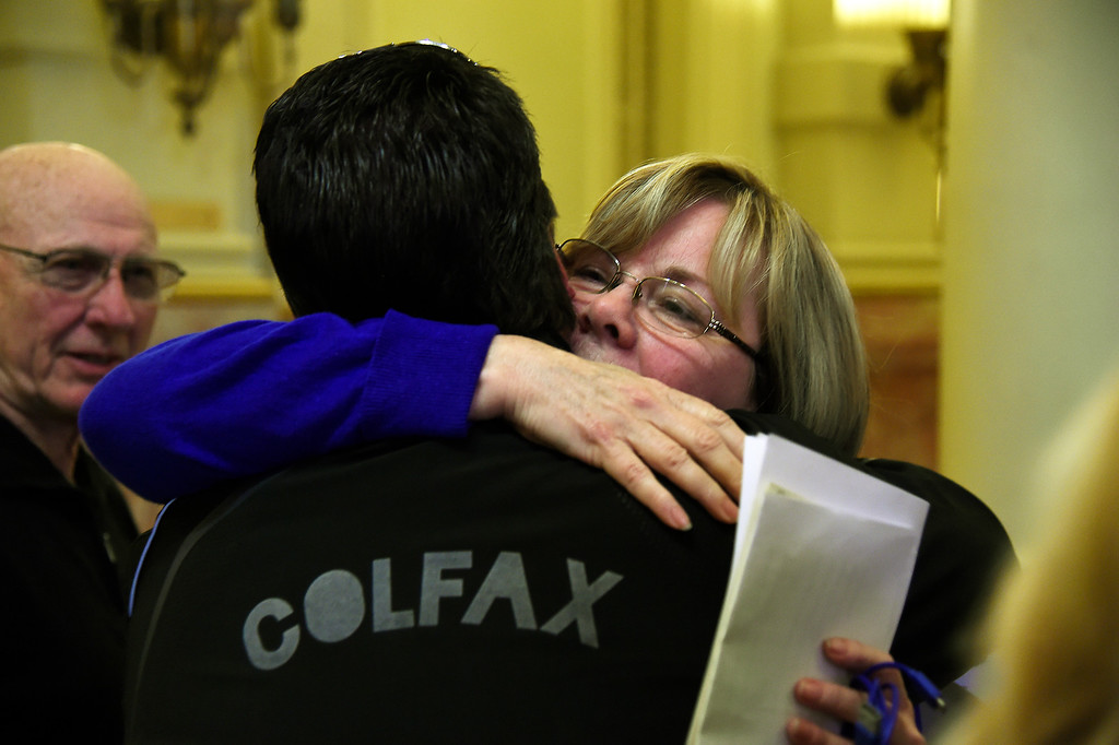 . DENVER, CO. - March 09, 2015: Lonnie Phillips watches as his wife Sandy hugs Dave Hoover after they gave testimony on the family members they lost during the theater shooting\'s in Aurora. The Senate Judiciary Committee listened to the public on Senate Bill 175, the bill repeals ammunition magazine limits imposed by the 2013 legislature. March 09, 2015 Denver, CO (Photo By Joe Amon/The Denver Post)