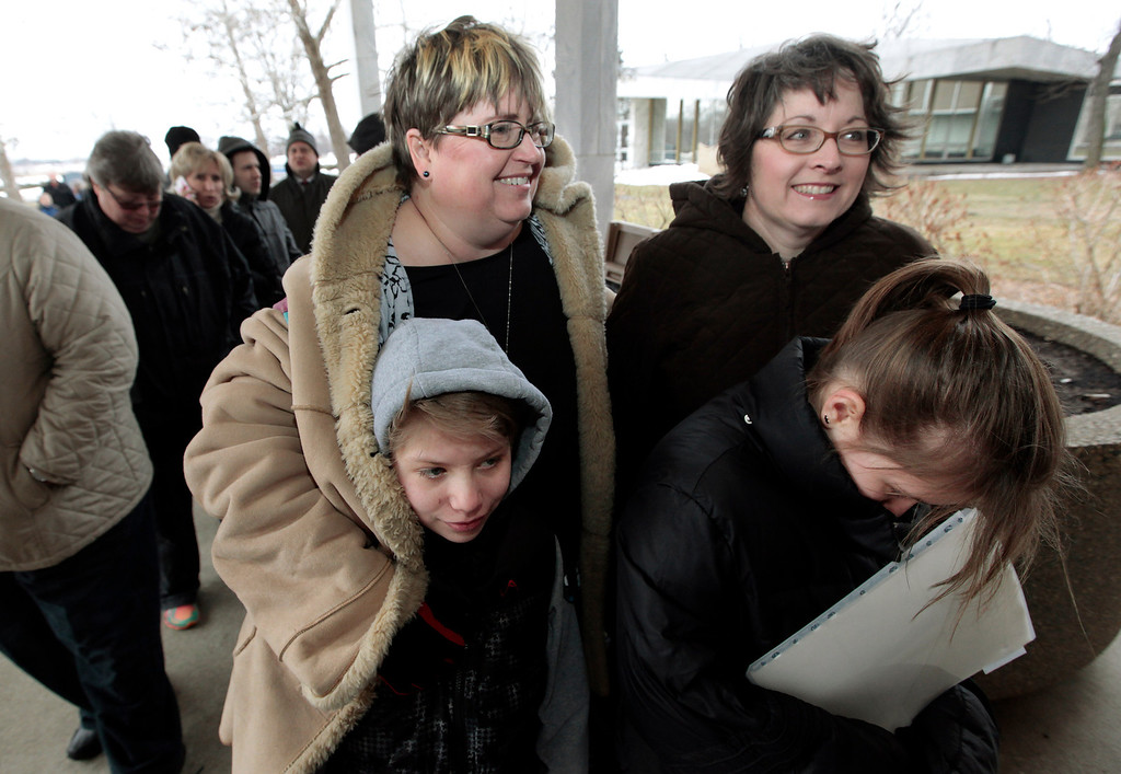 . Jenny Stanczyk, rear at left, and Cheryl Pine, rear at right, wait in line to apply for a marriage license at the Oakland County Clerks office with Maria , and Nina Stanczyk , front left and right, in Pontiac, Mich., Saturday, March 22, 2014. A federal judge has struck down Michigan\'s ban on gay marriage Friday the latest in a series of decisions overturning similar laws across the U.S. Some counties plan to issue marriage licenses to same-sex couples Saturday, less than 24 hours after a judge overturned Michigan\'s ban on gay marriage. (AP Photo/Paul Sancya)