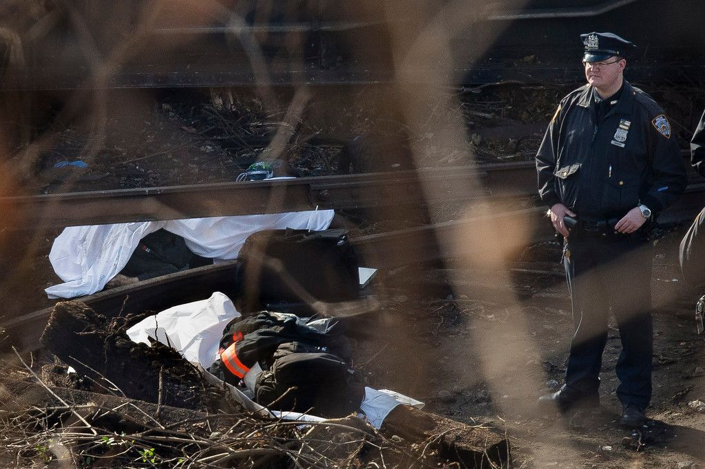 . A police officer stands guard over a body at the scene of a Metro-North passenger train derailment in the Bronx borough of New York, Sunday, Dec. 1, 2013. The train derailed on a curved section of track in the Bronx on Sunday morning, coming to rest just inches from the water and causing multiple fatalities and dozens of injuries, authorities said. (AP Photo/John Minchillo)
