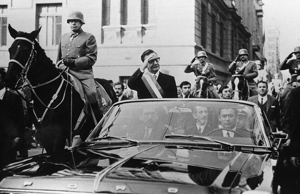 . Chilean President Salvador Allende (C) waves to their supporters in Santiago a few days after his election on October 24, 1970. The car with Allende is escorted by General Augusto Pinochet (L).  AFP PHOTOSTF/AFP/Getty Images