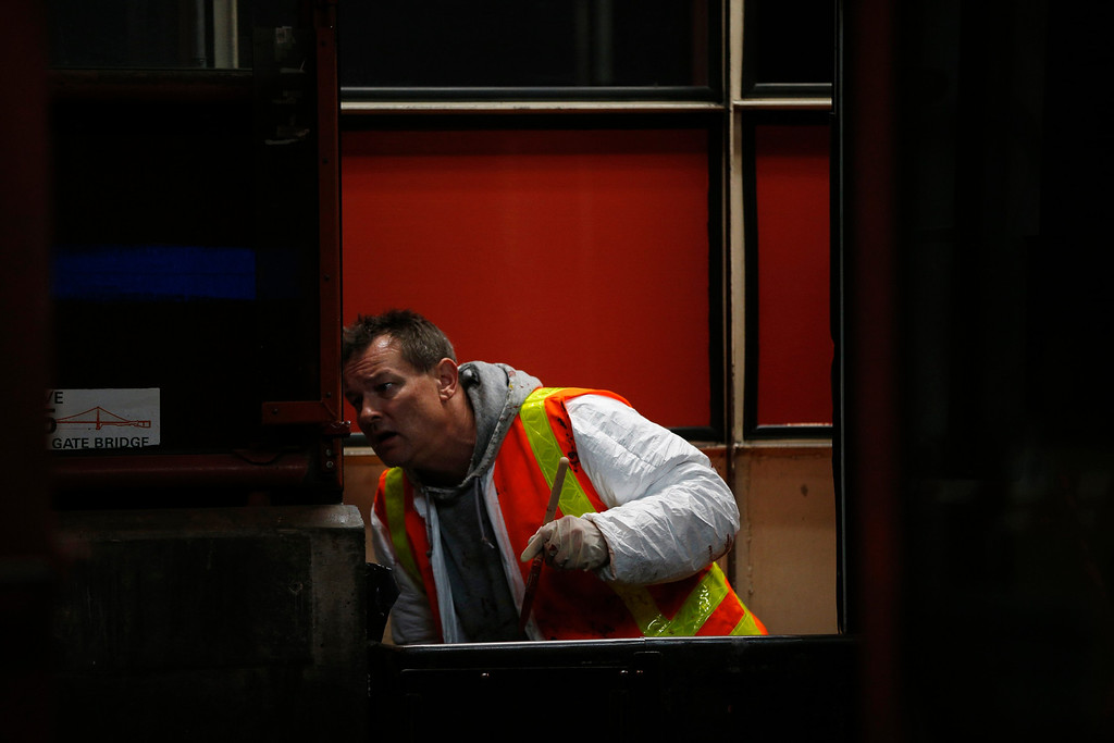 . A worker paints the window of a tollbooth at the Golden Gate Bridge toll plaza in San Francisco, California March 27, 2013. The Golden Gate Bridge will convert from manned tollbooths to a full electronic tolling system starting today. With the automated system in place, motorists will have the option of using the existing FasTrak electronic toll collection system or the newly implemented pay-by-plate option, according to the Golden Gate Bridge management. REUTERS/Stephen Lam