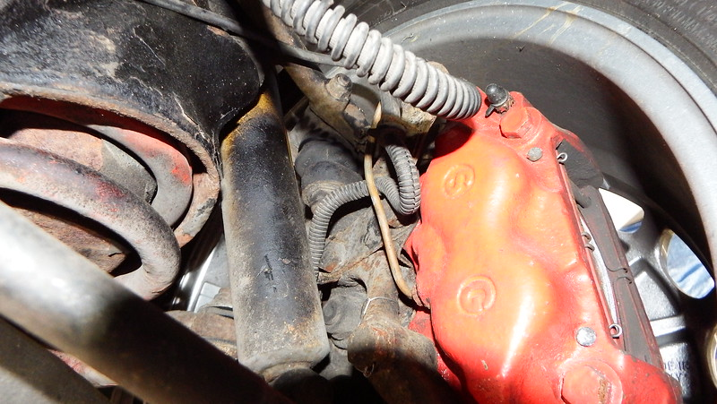 Right front caliper; ABS sensor lead incorrectly routed and probably damaged under brake pipe