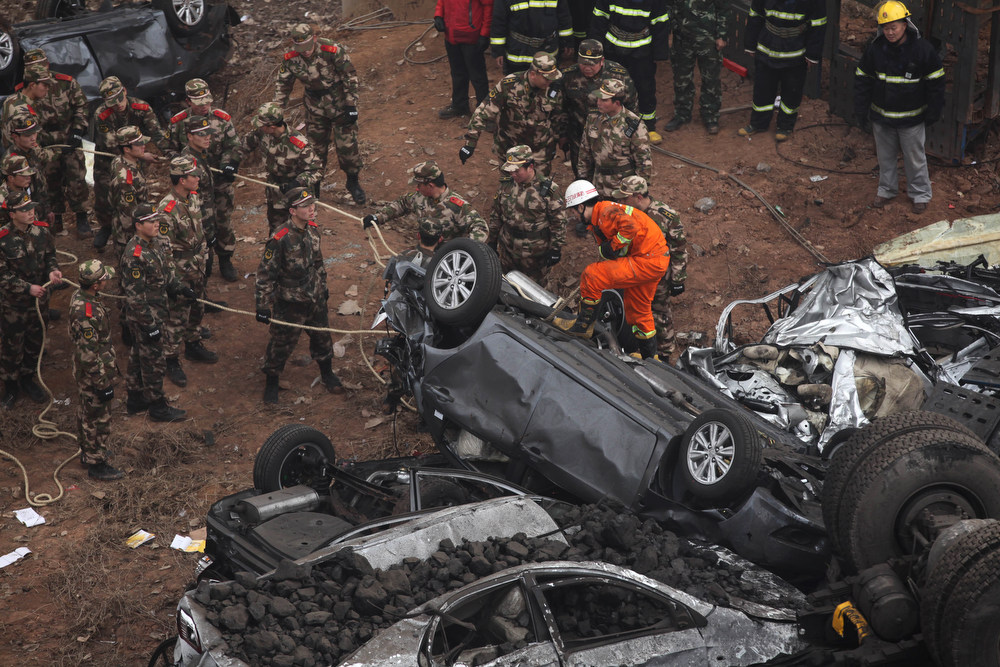 Description of . Rescuers pull a damaged car at the scene of the collapsed Yichang bridge near the city of Sanmenxia, central China's Henan province, on February 1, 2013 after a fireworks-laden truck exploded as it crossed the bridge killing 26 people as the structure collapsed and vehicles plummeted to the ground, state-run media reported. An 80-meter long part of the bridge collapsed and six vehicles had been retrieved from the debris, China's official news agency Xinhua said. The bridge near the city of Sanmenxia is on the G30 expressway, the longest road in China, which stretches for nearly 4,400 kilometers (2,700 miles) from China's western border with Kazakhstan to the eastern Yellow Sea. AFP PHOTO STR/AFP/Getty Images