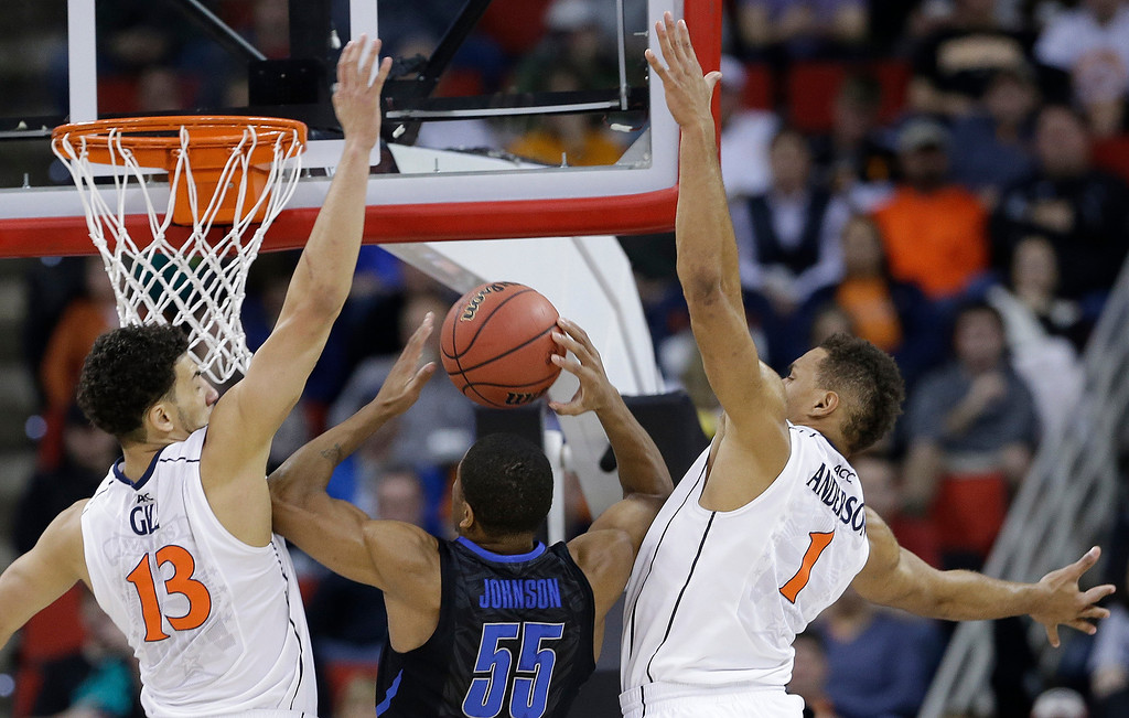 . Memphis guard Geron Johnson (55) shoots against Virginia\'s Anthony Gill (13) and Justin Anderson (1) during the first half of an NCAA college basketball third-round tournament game, Sunday, March 23, 2014, in Raleigh. (AP Photo/Gerry Broome)