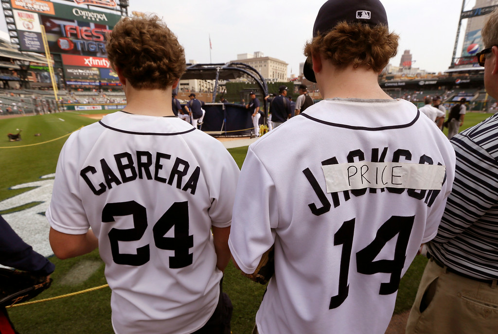 . Daniel Hackert, right, sporting an Austin Jackson turned into a temporary David Price jersey and his brother Alex, left, of Franklin, Mich., take in batting practice before an interleague baseball game between the Detroit Tigers and the Colorado Rockies, Saturday, Aug. 2, 2014, in Detroit. (AP Photo/Carlos Osorio)