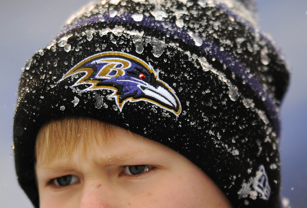 . A young Baltimore Ravens fan watches players warm up as snow falls before an NFL football game between the Ravens and the Minnesota Vikings, Sunday, Dec. 8, 2013, in Baltimore. A powerful storm system that spread snow, sleet and freezing rain widely across the nation\'s midsection rumbled toward the densely populated Eastern seaboard on Sunday, promising more of the same. (AP Photo/Gail Burton)
