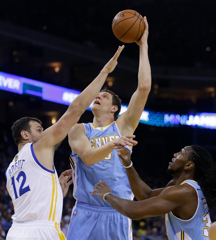 . Denver Nuggets\' Timofey Mozgov, center, shoots over Golden State Warriors\' Andrew Bogut (12) during the first half of an NBA basketball game Thursday, April 10, 2014, in Oakland, Calif. (AP Photo/Ben Margot)