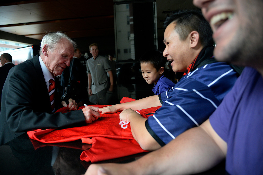 . DENVER, CO - JULY 24: Paddy Crerand, a former Manchester United player who helped the squad to to English League titles, signs an autograph for Jui Lim and his son, Aaron (6), as the team arrives at their hotel. Manchester United will play Italian squad Roma on Saturday, July 26 and arrived in Denver on Thursday, July 24, 2014. (Photo by AAron Ontiveroz/The Denver Post)