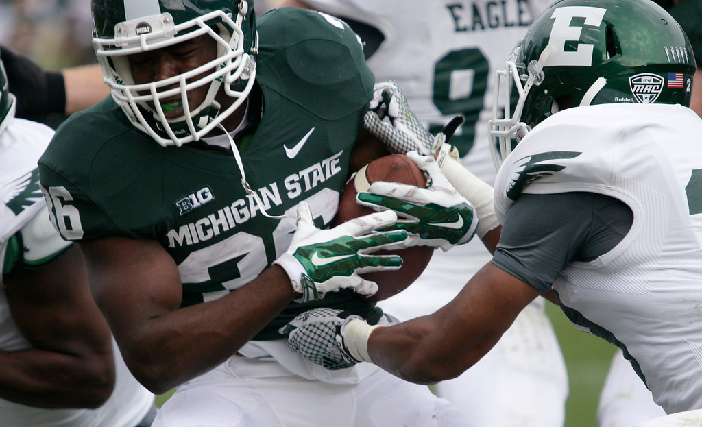 . Michigan State\'s Philip-Michael Williams, left, rushes against Eastern Michigan\'s Jason Beck during the fourth quarter of an NCAA college football game, Saturday, Sept. 20, 2014, in East Lansing, Mich. Michigan State won 73-14. (AP Photo/Al Goldis)