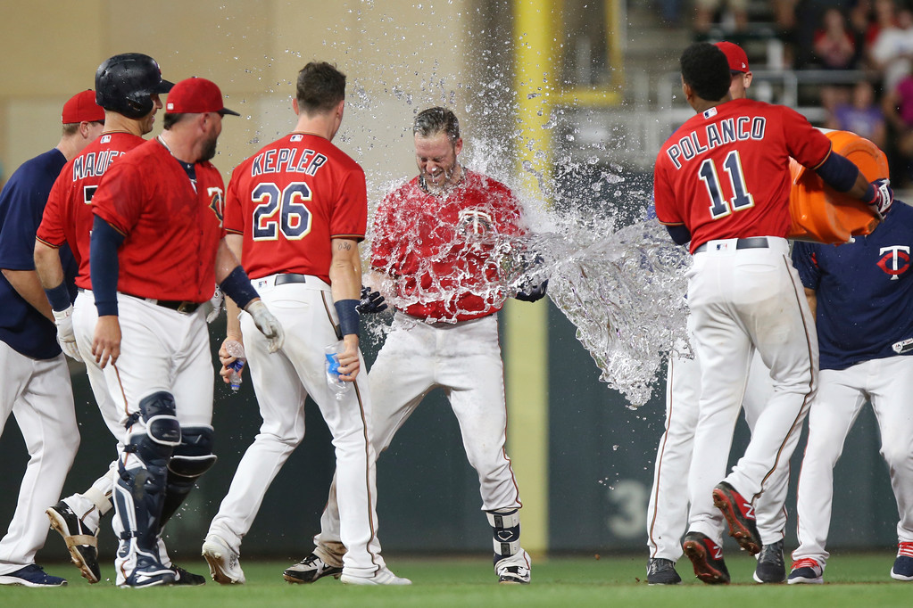 . Minnesota Twins\' Jorge Polanco throws water on teammate Mitch Graver after Graver\'s fly ball to left field to win the game against the Cleveland Indians in a baseball game, Monday, July 30, 2018 in Minneapolis. Minnesota won 5-4. (AP Photo/Stacy Bengs)