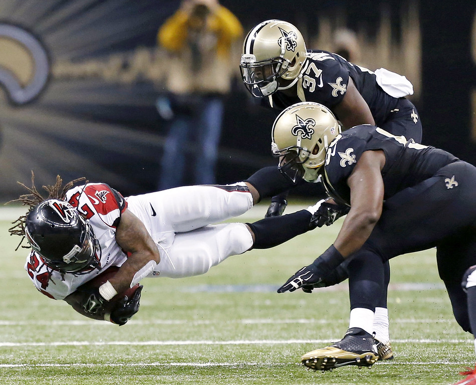 . Atlanta Falcons running back Devonta Freeman (24) is tackled by New Orleans Saints defensive back Terrence Frederick (37) in the second half of an NFL football game in New Orleans, Sunday, Dec. 21, 2014. (AP Photo/Rogelio Solis)