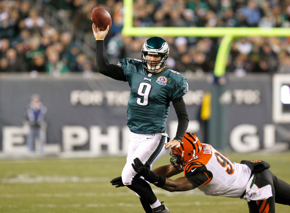 Description of . Philadelphia Eagles quarterback Nick Foles (L) releases a pass as Cincinnati Bengals defensive end Carlos Dunlap tries to tackle him during their NFL football game in Philadelphia, Pennsylvania, December 13, 2012.  REUTERS/Tim Shaffer