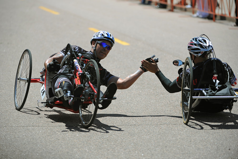 . Ronnie Jimenez high fives a competitor after winning the Men\'s 10K hand cycle race in 21:53.  The fourth annual Warrior Games cycling event took The fourth annual Warrior Games cycling event took started and finished at Falcon Stadium on the grounds of the Air Force Academy in Colorado Springs, CO on May 12, 2013.  HRH Prince Harry was on hand to start the race as well as to hand out medals at the finish line.   A total of 260 wounded, ill and injured service members and veterans came to compete in the week long games.  Members of the Army, Marine Corps, Navy/Coast Guard/Air Force. Special Operations and the British Armed Forces all took part in the competition.  Other events included in the Warrior Games are shooting, sitting volleyball, track & field and wheelchair basketball.  (Photo by Helen H. Richardson/The Denver Post)