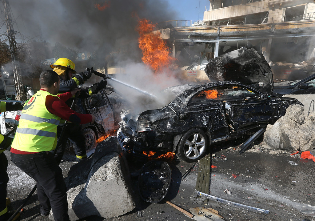 . Lebanese firefighters extinguish a burning car at the site of an explosion near the Kuwaiti Embassy and Iran\'s cultural center, in the suburb of Beir Hassan, Beirut, Lebanon, Wednesday, Feb. 19, 2014.  (AP Photo/Hussein Malla)