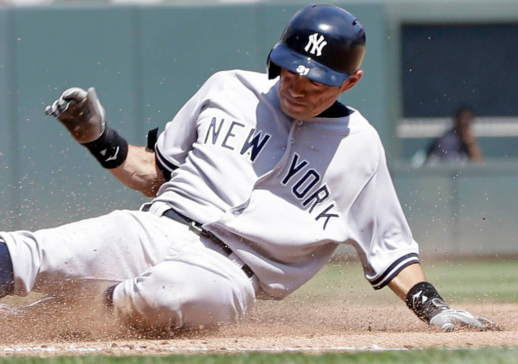 . New York\'s Ichiro Suzuki slides safely into third with a triple off Minnesota relief pitcher Brian Duensing in the sixth inning.  (AP Photo/Jim Mone)