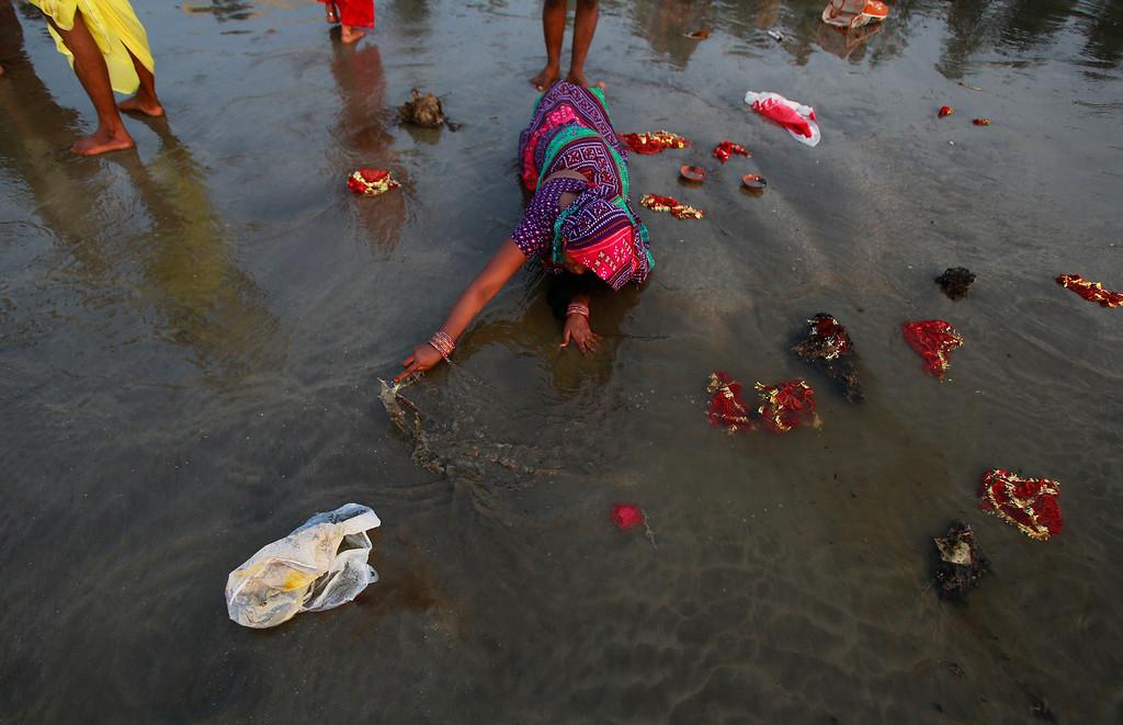. Hindu devotees move while lying prostrate, as part of a ritual, towards the Arabian Sea during Chhath Puja festival in Mumbai, India, Friday, Nov. 8, 2013. (AP Photo/Rafiq Maqbool)
