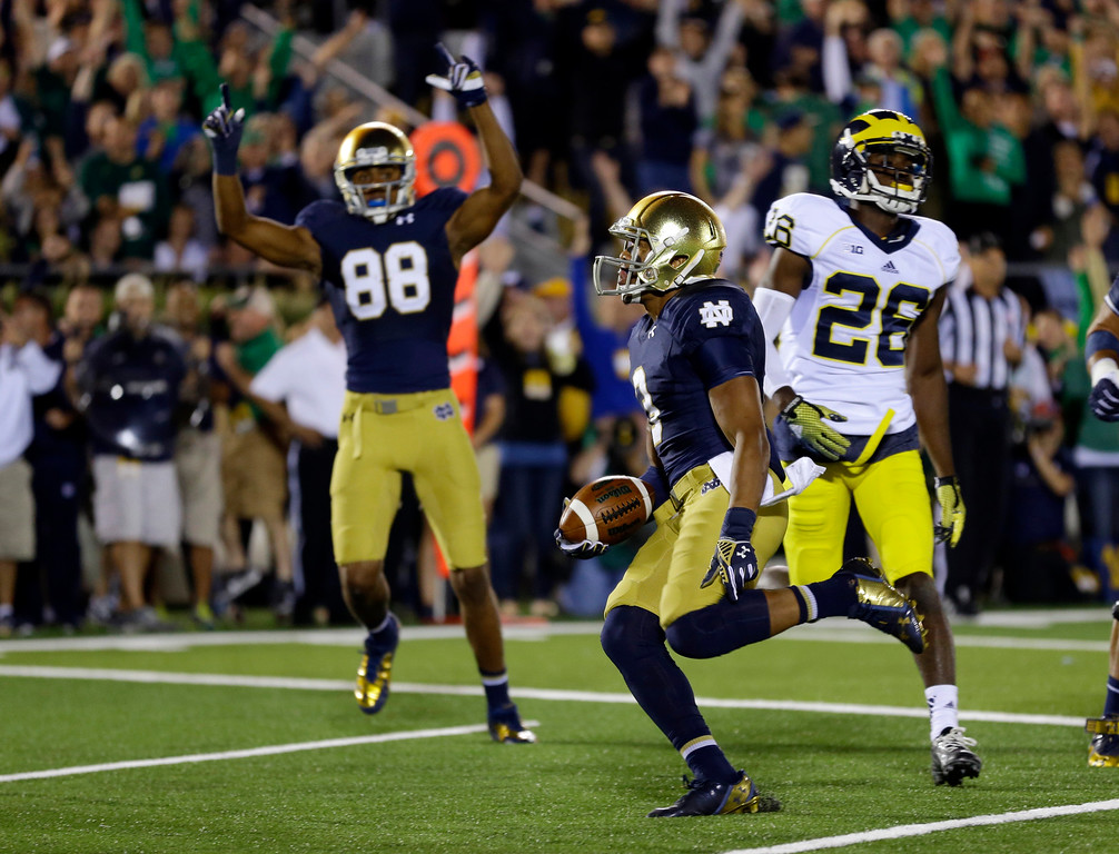 . Notre Dame wide receiver Amir Carlisle runs in for a touchdown in front of teammates wide receiver Corey Robinson and Michigan defensive back Jourdan Lewis during the second half of an NCAA college football game in South Bend, Ind., Saturday, Sept. 6, 2014. (AP Photo/Michael Conroy)