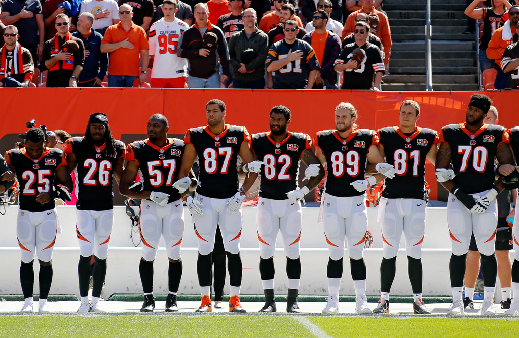 . Cincinnati Bengals players lock arms during the national anthem before an NFL football game against the Cleveland Browns, Sunday, Oct. 1, 2017, in Cleveland. (AP Photo/Ron Schwane)