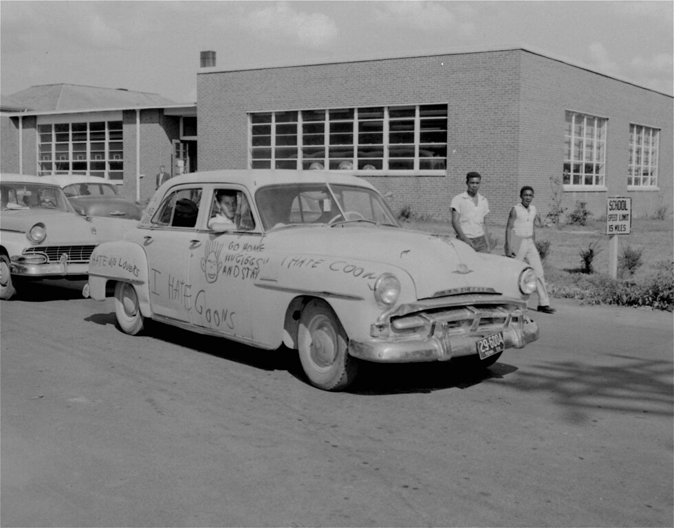 . Two unidentified black students walk past a car lettered with anti-integration slogans and drawings as Clinton High School, Clinton, Tennessee, ended its first week of integration August 31, 1956.  There have been some incidents of minor violence involving whites and blacks as a result of the court ordered integration, but the tension had eased today.  (AP Photo/Gene Herrick)