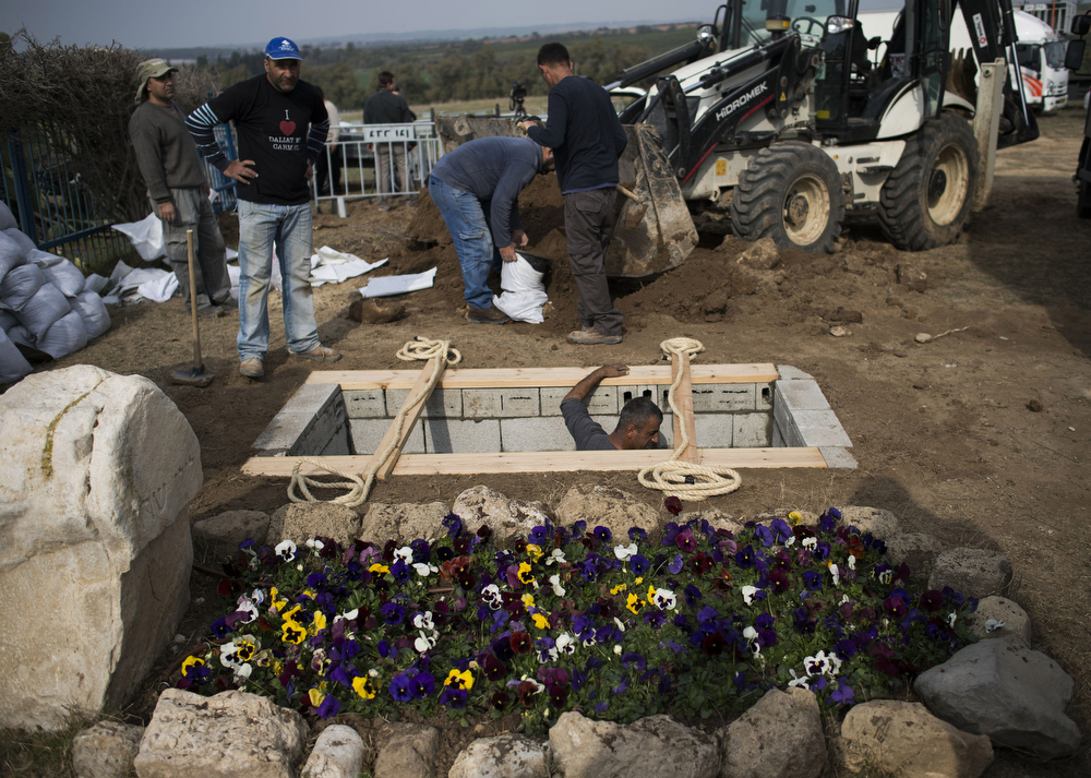 . Workers prepare the grave of late former PM Ariel Sharon next to his wife Lili Sharon\'s grave on January 12, 2014 in Havat Hashikmim, Israel.(Photo by Ilia Yefimovich/Getty Images)