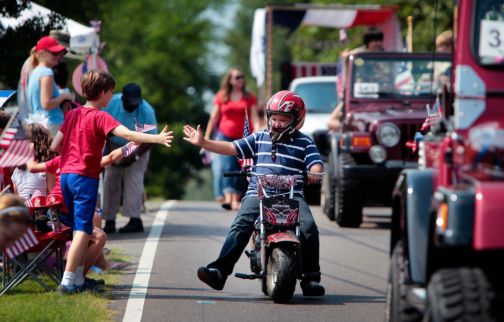 . Patrick Ardis, 10, gets a high-five from his friend Porter Rosenberg, 10, left, while riding in the Cordova Independence Day Parade at the Cordova Community Center in Cordova, Tenn., on Thursday, July 4, 2013.  (AP Photo/The Commercial Appeal, Jim Weber)