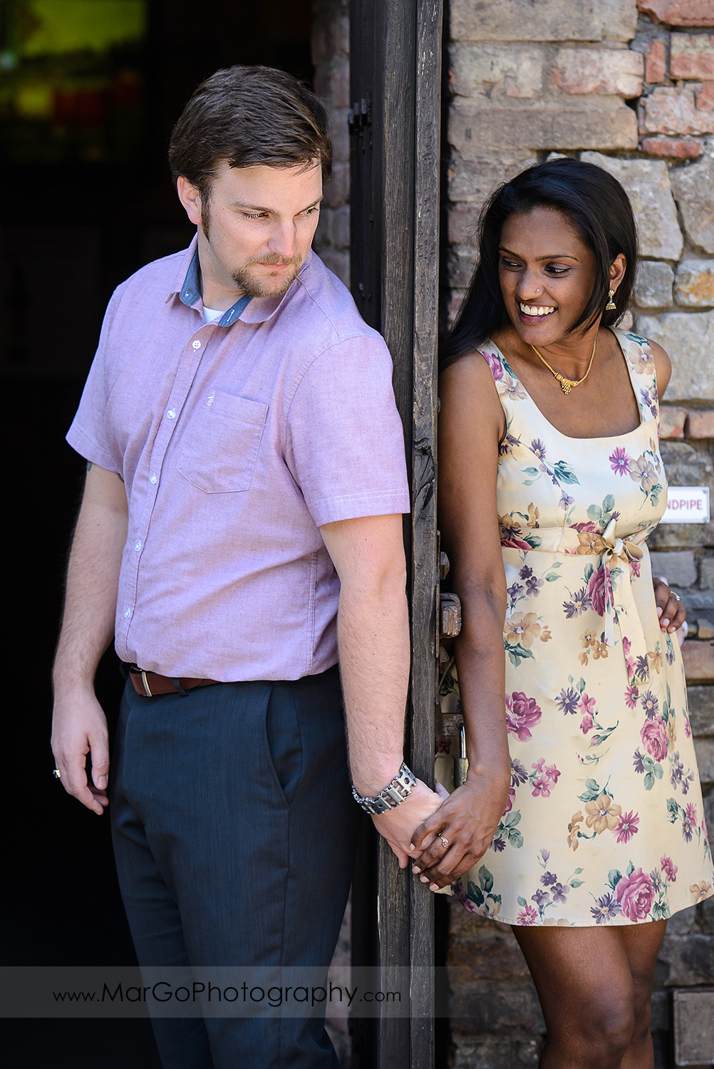 man in pink shirt and Indian woman in flower dress standing on the opposite sides of the door and holding hands during engagement session at Castello di Amorosa in Calistoga