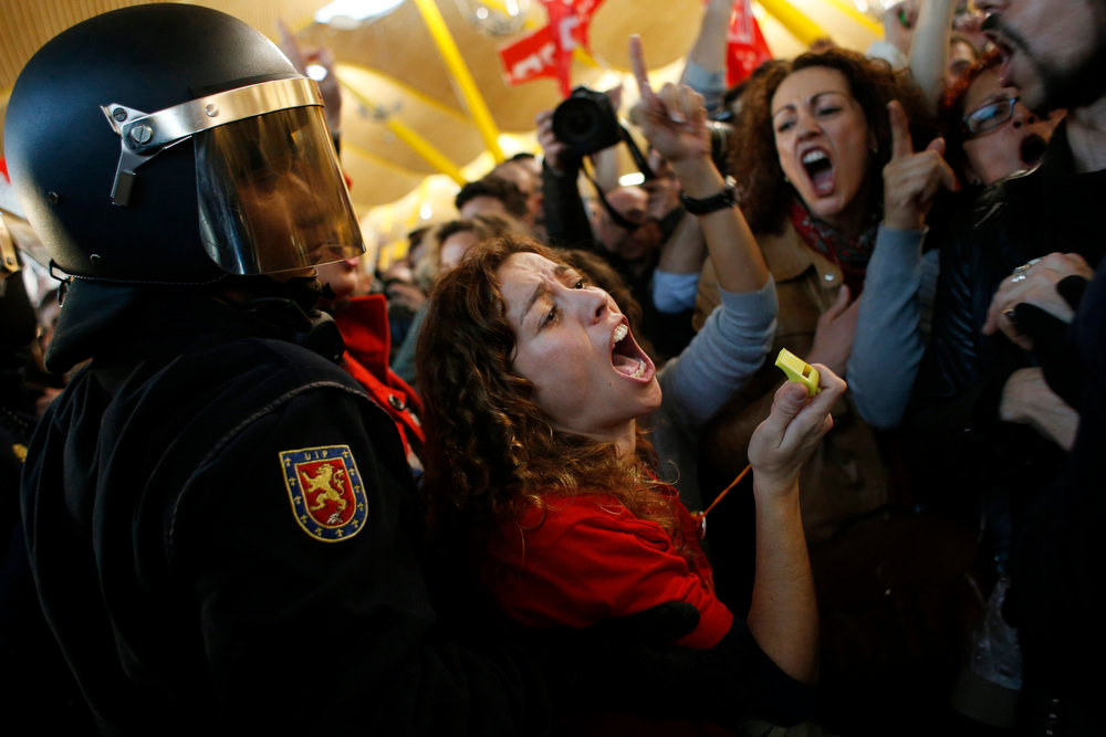 . An Iberia airline worker reacts as she is pushed away by Spanish riot police officers during a strike at Madrid\'s Barajas airport February 18, 2013. Striking union workers clashed with police at the airport on Monday on the first day of a week-long strike over more than 3,800 pending job cuts at Spain\'s flagship airline Iberia. REUTERS/Susana Vera