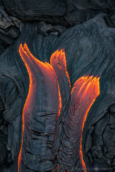 Lava flows create abstract patterns below Kilauea's Pu'u O'o Crater, on the big island of Hawaii. Helicopter shot looking straight down.