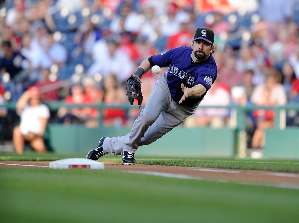 . Colorado Rockies first baseman Todd Helton tosses the ball to Tyler Chatwood, not seen, to get out Washington Nationals\' Denard Span out at first on a grounder during the first inning of a baseball game, Friday, June 21, 2013, in Washington. (AP Photo/Nick Wass)