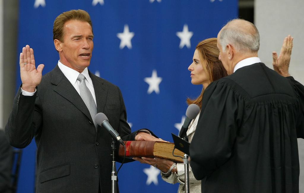 . SACRAMENTO, CA - NOVEMBER 17:  Arnold Schwarzenegger is sworn in as the 38th governor of California by California Chief Justice Ronald George (R) as Schwarzenegger\'s wife, Maria Shriver (C), looks on November 17, 2003 in Sacramento, California. Schwarzenegger defeated former California governor Gray Davis in a historic recall election in October.  (Photo by Justin Sullivan/Getty Images)