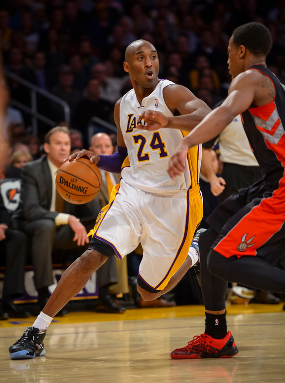 . Lakers� Kobe Bryant drives around Raptors� DeMar DeRozan during first half action at Staples Center Sunday, December 8, 2013.   ( Photo by David Crane/Los Angeles Daily News )
