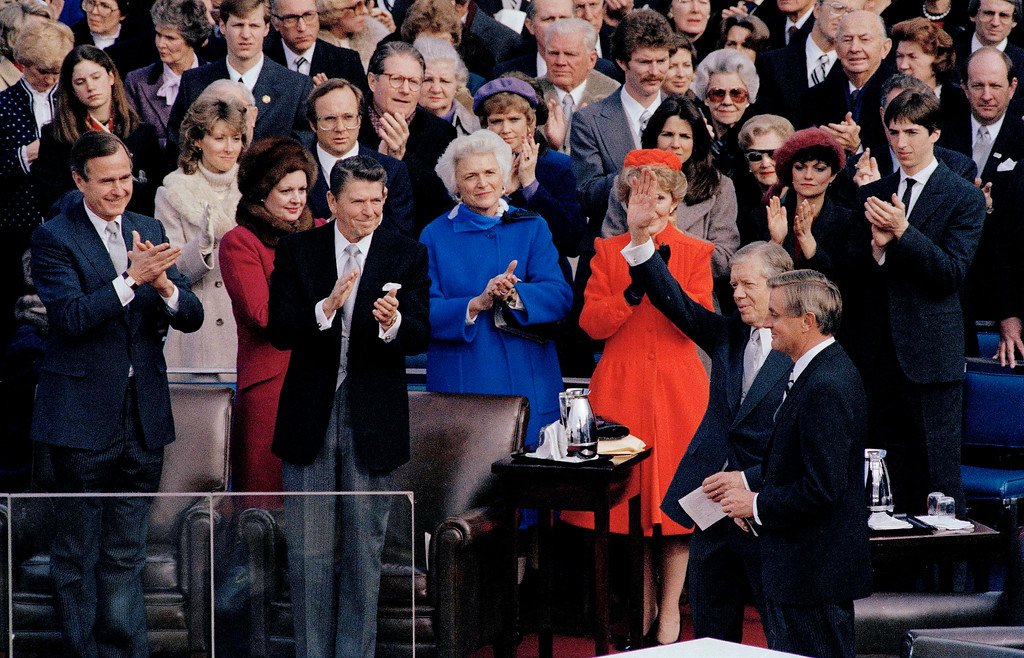 . Outgoing President Jimmy Carter waves to the crowd at the inauguration of 40th President Ronald Reagan in Washington, D.C., Jan. 20, 1981. In the background, new Vice President George Bush, Reagan, Barbara  Bush and first lady Nancy Reagan applaud. Next to Carter is outgoing Vice President Walter Mondale, and at far right, Reagan\'s son Ron applauds. (AP Photo)