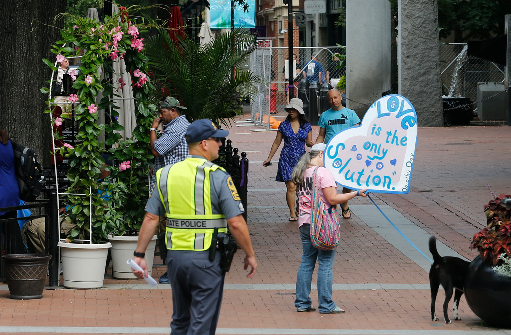 . A visitor carries a sign as State Police lock down the downtown area in anticipation of the anniversary of last year\'s Unite the Right rally in Charlottesville, Va., Saturday, Aug. 11, 2018. The Governor has declared a state of emergency in Charlottesville. (AP Photo/Steve Helber)