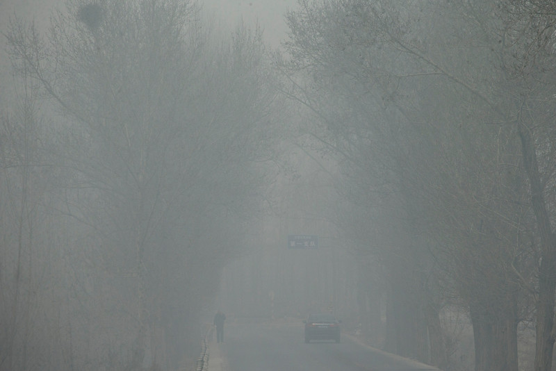 . A man and a car traveling on a road are obscured in heavy haze on a severely polluted day in Pingshan county of Shijiazhuang, in northern China\'s Hebei province, Wednesday, Feb. 26, 2014. (AP Photo/Alexander F. Yuan)
