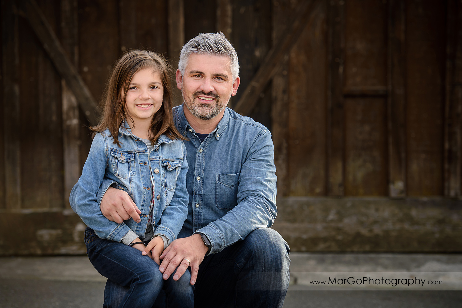 horizontal portrait of father and daugher sitting on his lap wearing jeans shirts and looking into camera with wooden backdrop during family session at Old Borges Ranch in Walnut Creek