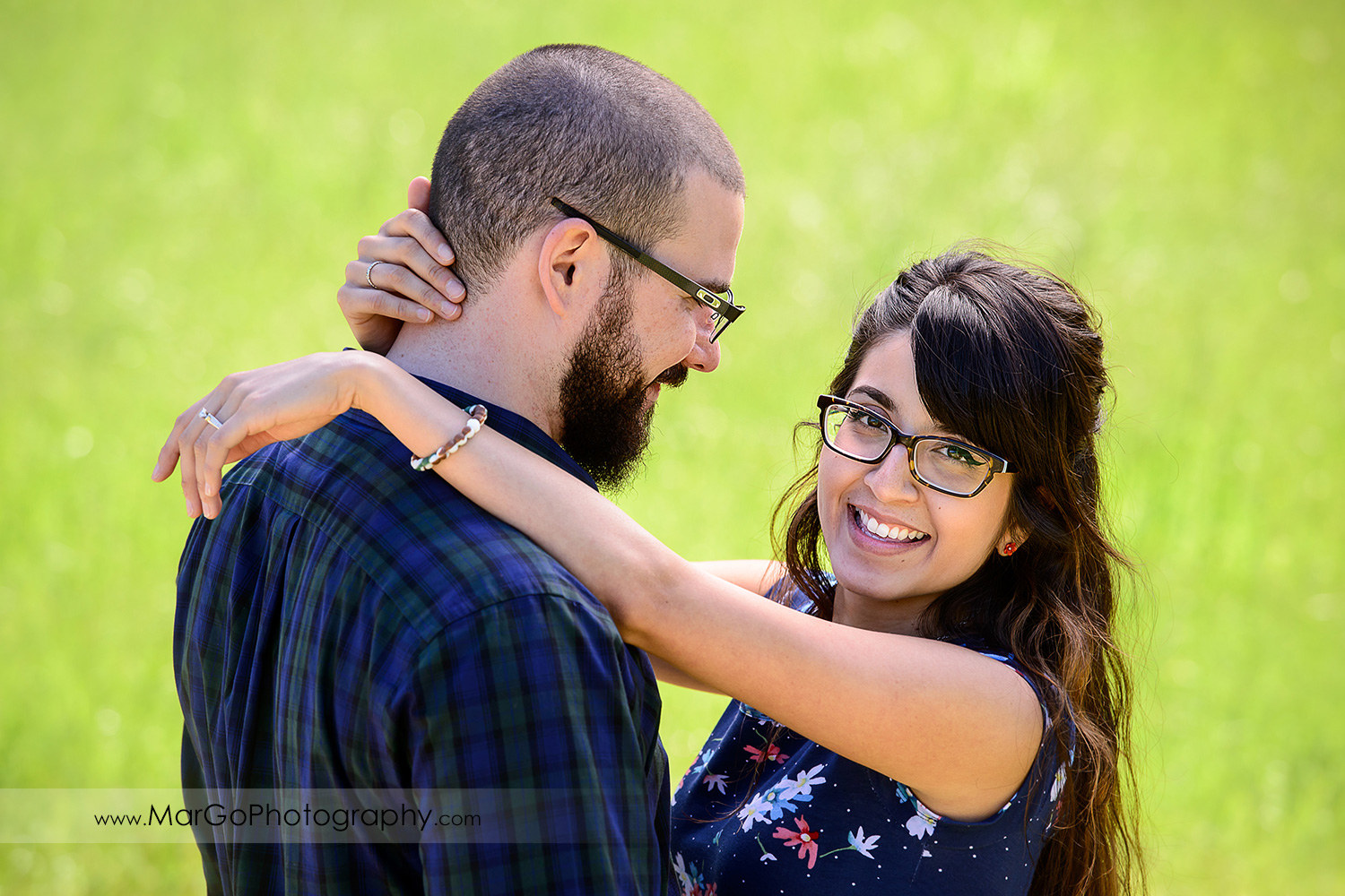 close-up portrait of man in blue shirt looking at woman in blue dress looking into camera on the green grass backround during engagement session at Sunol Regional Wilderness
