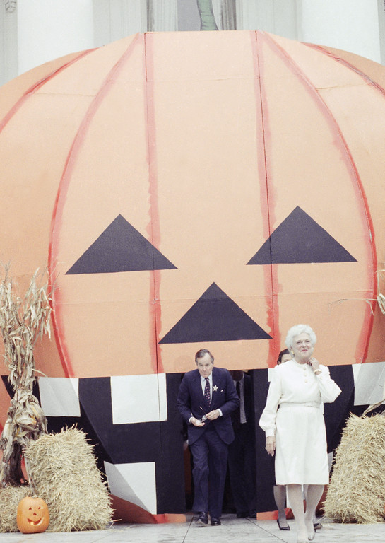 . President George H. W. Bush and wife Barbara, emerge from a giant pumpkin on the South Lawn of the White House Oct. 31, 1989 in Washington, where they hosted a Halloween party for local school kids. (AP Photo/Barry Thumma)