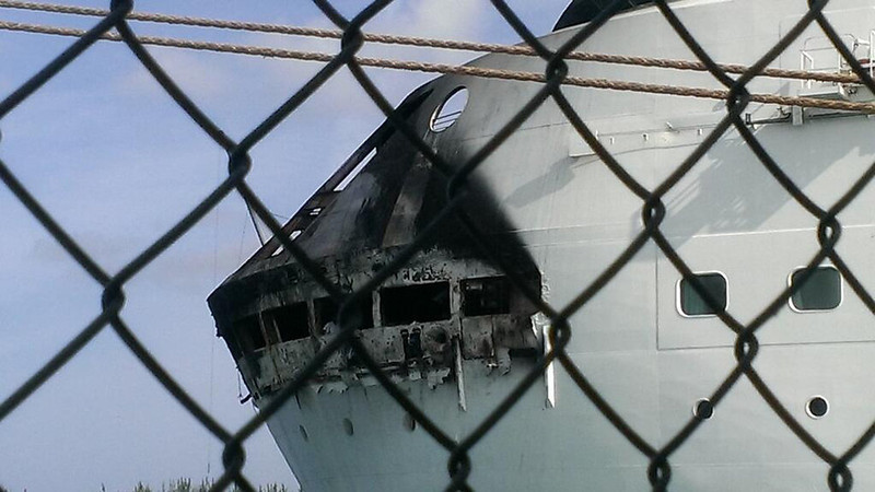 . This photo provided by Royal Caribbean shows the fire-damaged exterior of Royal Caribbean\'s Grandeur of the Seas cruise ship, in Freeport, Bahamas. Royal Caribbean says the fire occurred on the mooring area of Deck 3 about 2:15 a.m. Monday, May 27, 2013, and was quickly extinguished, as the ship was en route to the Bahamas. Passengers and crew members reported to evacuation stations. No injuries were reported. (AP Photo/Royal Caribbean)