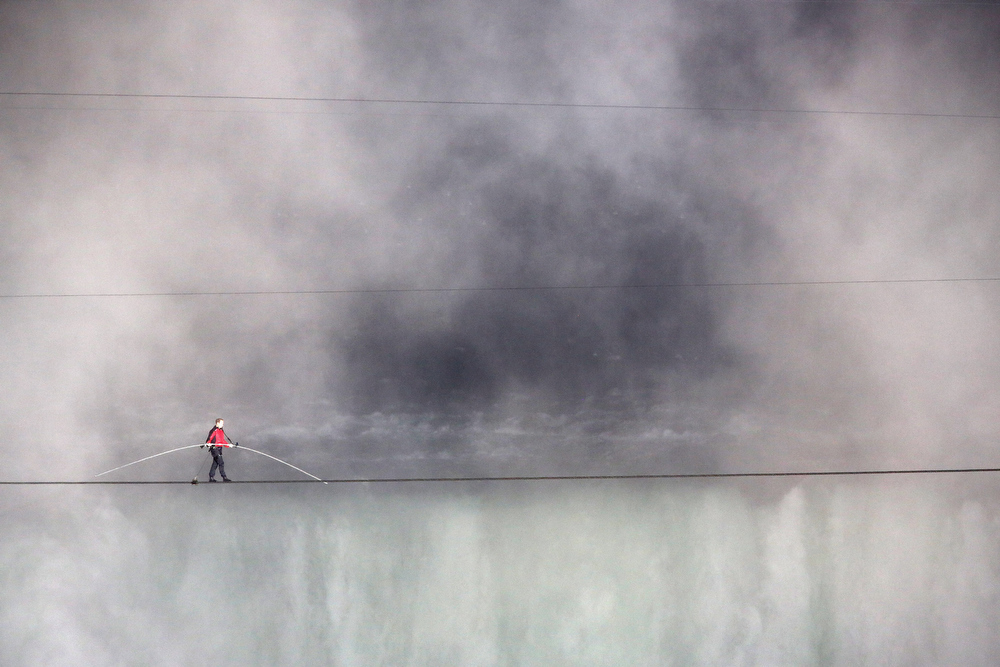 Description of . Aerialist Nik Wallenda tighropes over the Niagara Falls June 15, 2012 in Niagara Falls, Canada. Wallenda walked across the 1,800 foot long, 2 inch-wide wire Friday night as the first person to cross directly over the falls from the U.S. into Canada. Wallenda, 33 and a father of three, is a seventh generation member of the famed Flying Wallendas who trace their roots to 1780 Austria-Hungary, when ancestors traveled as a band of acrobats, aerialists, jugglers, animal trainers and trapeze artists. ABC televised the event and insisted the daredevil wear a teathered harness to prevent live coverage of a potentially deadly fall 190 feet into the churning torrent below. (Photo by John Moore/Getty Images)