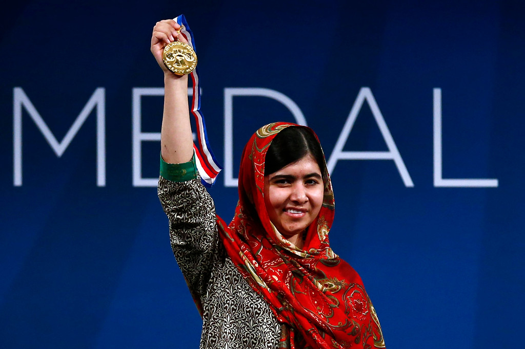 . Malala Yousafzai holds up her Liberty Medal during a ceremony at the National Constitution Center, Tuesday, Oct. 21, 2014, in Philadelphia. The honor is given annually to an individual who displays courage and conviction while striving to secure liberty for people worldwide. (AP Photo/Matt Rourke, File)