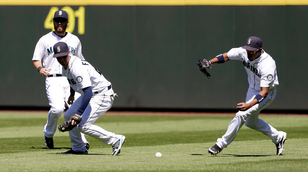 . Seattle Mariners right fielder Endy Chavez, right, races to the ball hit by Minnesota Twins\' Chris Colabello that fell between center fielder Dustin Ackley, left, and second baseman Nick Franklin in the fourth inning. (AP Photo/Elaine Thompson)