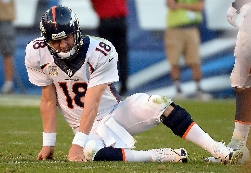 . Denver Broncos quarterback Peyton Manning (18) sits on the turf after going down and grabbing his ankle in the fourth quarter against the San Diego Chargers at Qualcomm Stadium. (Photo by John Leyba/The Denver Post)