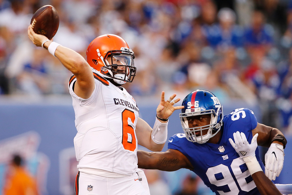 . Cleveland Browns quarterback Baker Mayfield (6) throws a pass away from New York Giants\' Kareem Martin (96) during the first half of a preseason NFL football game Thursday, Aug. 9, 2018, in East Rutherford, N.J. (AP Photo/Adam Hunger)