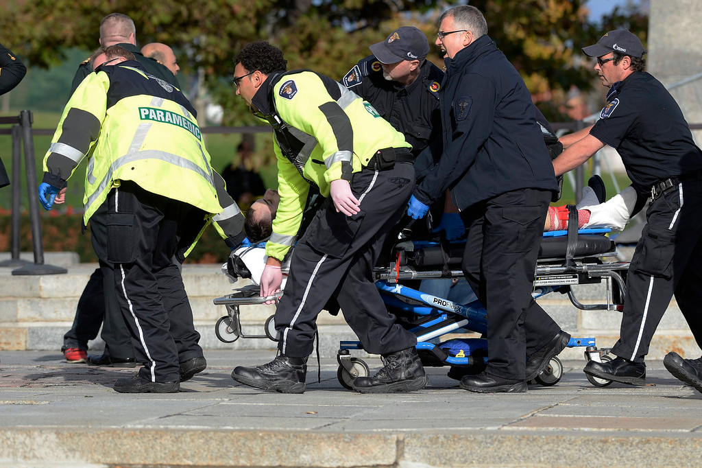 . Paramedics and police pull a victim away from the Canadian War Memorial in Ottawa, Ontario, on Wednesday, Oct. 22, 2014. A soldier standing guard at the National War Memorial was shot by an unknown gunman and people reported hearing gunfire inside the halls of Parliament. Prime Minister Stephen Harper was rushed away from Parliament Hill to an undisclosed location, according to officials. (AP Photo/The Canadian Press, Adrian Wyld)