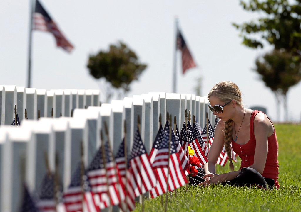 . Robyn Smith sits at the grave of her grandfather, Marine Cpl. veteran Robert Louman during a Memorial Day visit to the Sacramento Valley National Cemetery in Dixon, Calif., Monday, May 26, 2014.(AP Photo/Rich Pedroncelli)