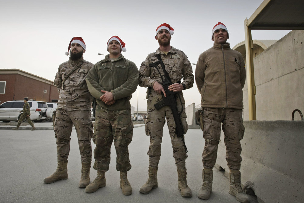 Description of . Spanish and U.S. soldiers with the NATO-led International Security Assistance Force (ISAF) wearing Santa Claus hats pose for a photograph on Christmas eve at the U.S.-led coalition base in Kabul, Afghanistan, Monday, Dec. 24, 2014. (AP Photo/Musadeq Sadeq)